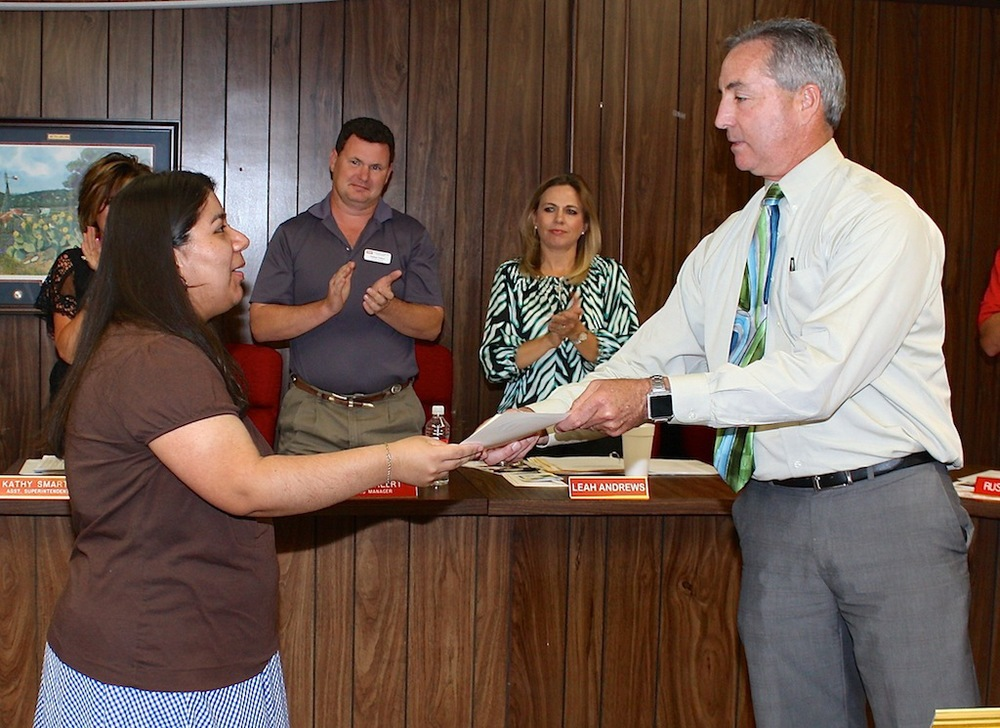 The Sweetwater Reporter's Belinda Serrano receives a formal resolution from Superintendent Terry Pittman for making the TASB Media Honor Roll