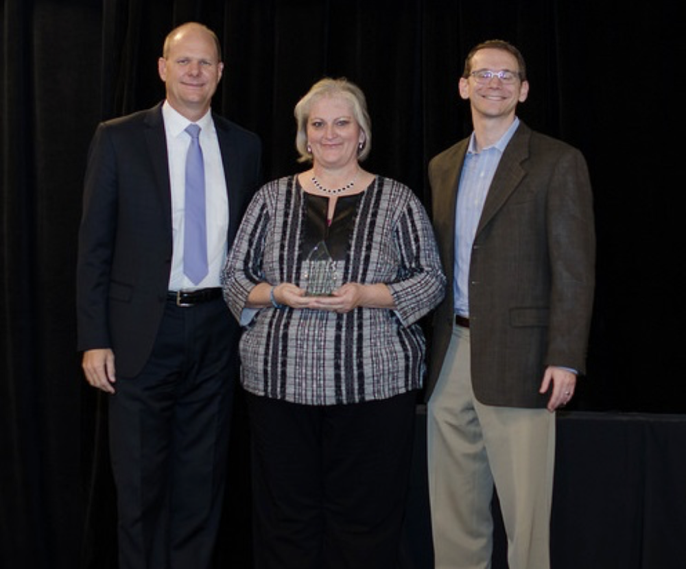 Kathy Witt receives her award from TASA President Kevin Brown (left) and Texas Commissioner of Education Mike Morath.