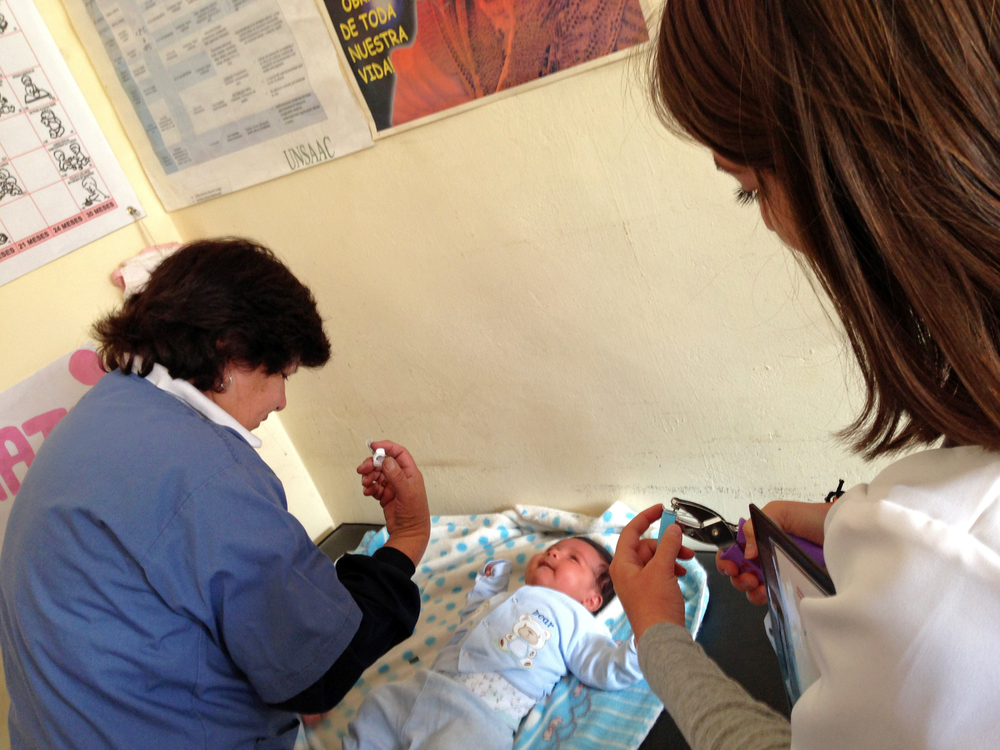 Wondering what it's like to work on our pilot study in Cusco? Check out this blog by one of our summer interns, Dani Corona (on right) by clicking on the photo.Here, Dani hole-punches out the symbols on the bracelet that correspond to the vaccines being administered to this 2-month-old. Photo taken: May 1, 2013.