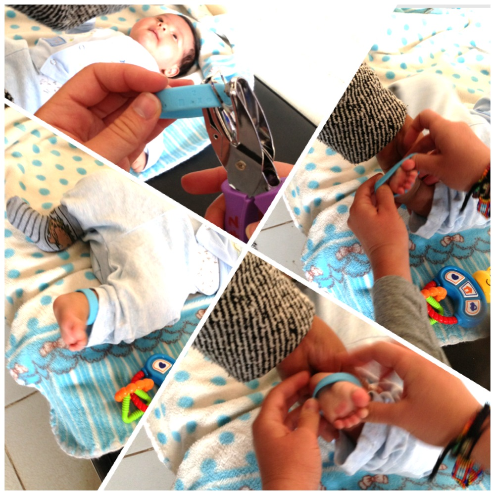 Step-by-step of one of our interns hole-punching out the vaccine symbols and then putting the bracelet on a 2-month-old baby boy's ankle. His mother was so excited to receive a bracelet!     Photo taken: June 1, 2013.