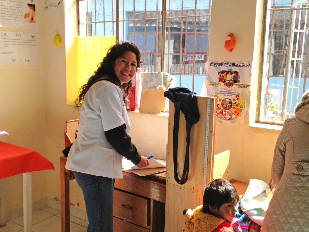 Vanessa Rivera, a summer intern, records data about an infant she's enrolling at the Belenpampa clinic in Cusco. Photo taken: June 1, 2013.