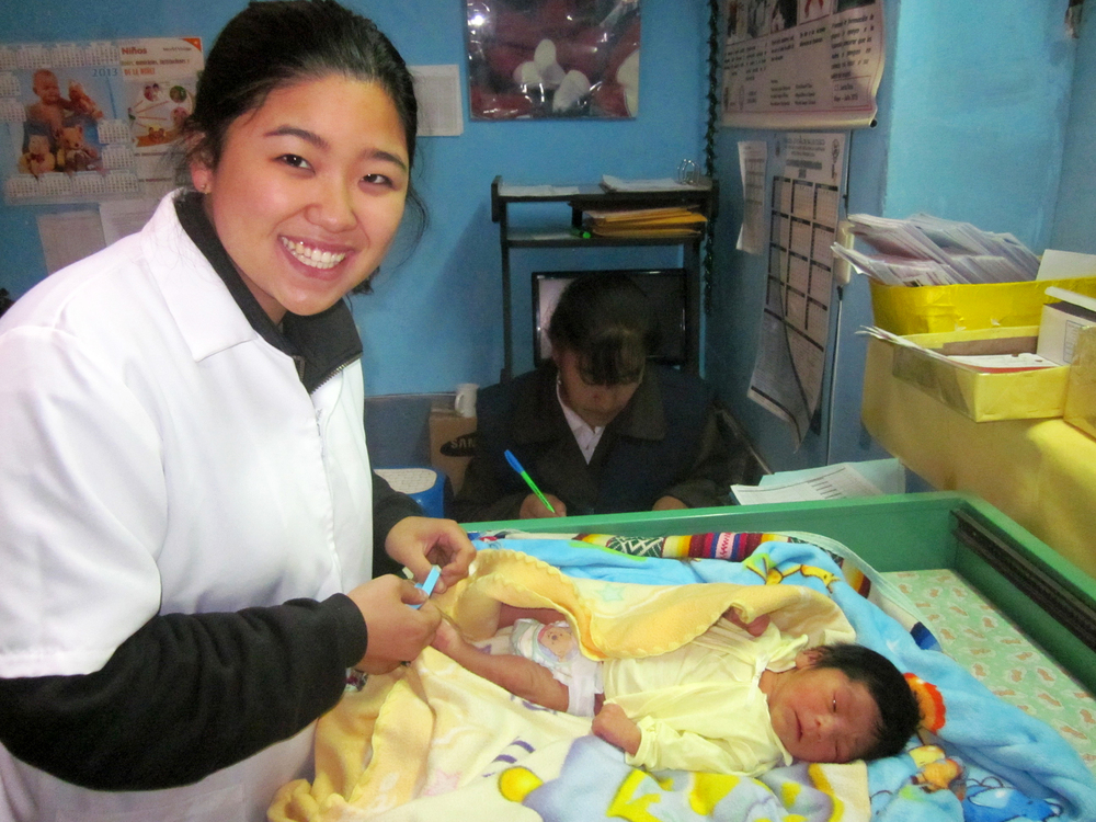 Joanie Kim, a summer intern, enrolling one half of a set of twins at the Santa Rosa health clinic in Cusco!     Photo taken: June 17, 2013.