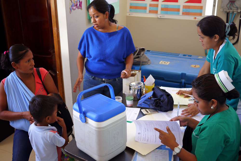 Guadalupe, a Ministry of Public Health vaccine expert, explains to this mother and two nurses how to use the bracelet and answers the mother's questions. Photo taken: June 25, 2013.