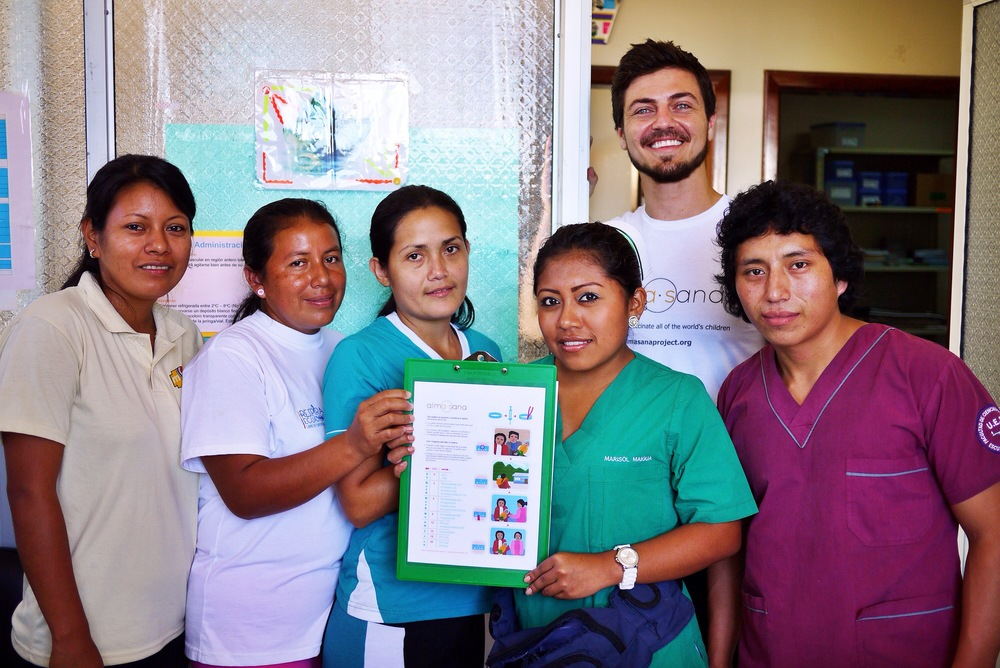 Alex Bozzette (in Alma Sana shirt), our Ecuador Project Coordinator, with the health center immunization nurses who also served as our study staff. Here they're presenting the locally adapted vaccine symbol guide for low-income moms. Photo taken: June 25, 2013.