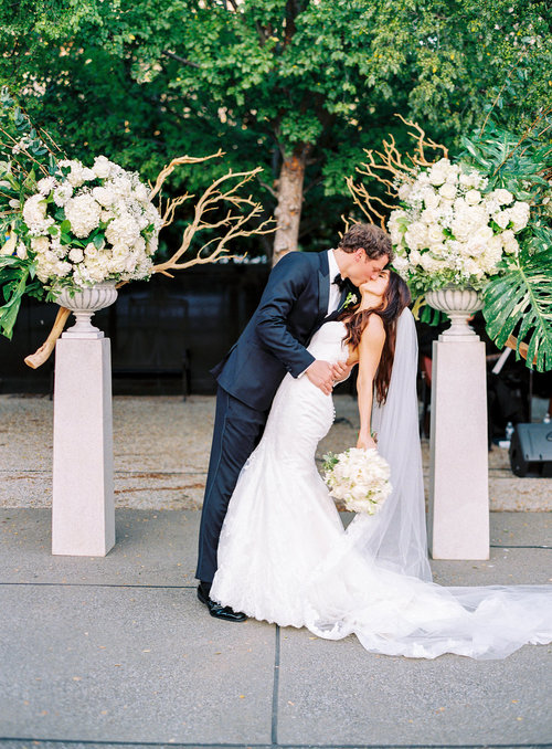 The groom kissing his bride after their wedding at the Frist Center for the Visual Arts in downtown Nashville, TN. Wedding planning & design by Big Events Wedding.