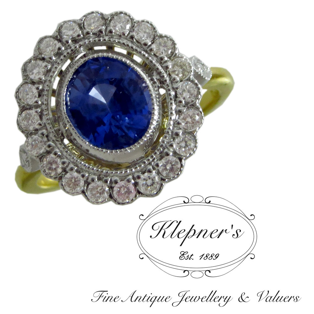 Sapphire and diamond daisy cluster style engagement ring.