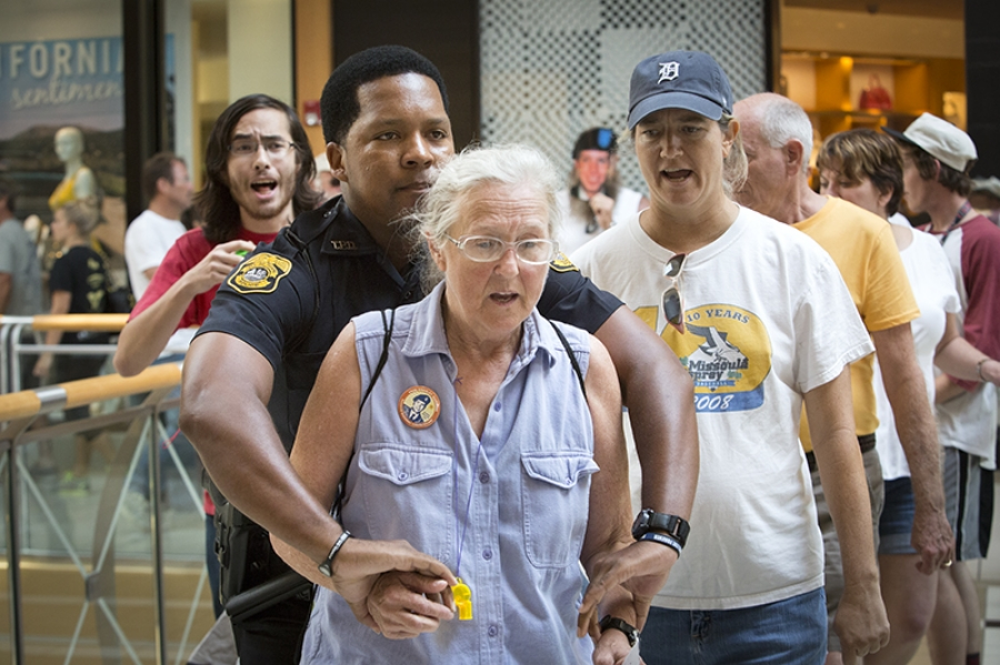 Susie Shannon of Occupy Tampa escorted out of International Plaza in Tampa on 07-27-13 after participating in a demonstration protesting the jailing of Bradley Manning, the Army private and  former intelligence analyst being held for his alleged release of classified information to the web site WikiLeaks.