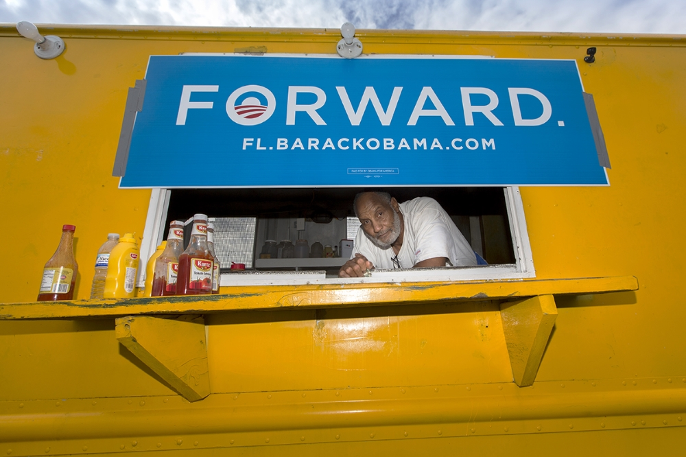 """James """"Pictureman"""" Youngblood peers from his food truck, where he and wife Sheilah gave away hot dogs across the street from the College Hill polling place in Tampa on election day."""