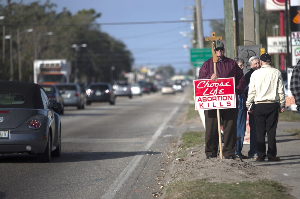 Jim Haskins holds a crucifix with a choose life sign attached outside of the Women's Health Center on Fletcher Ave in Tampa. The image was part of a story being done for the 40th anniversary of Roe v. Wade by Arielle Stevenson