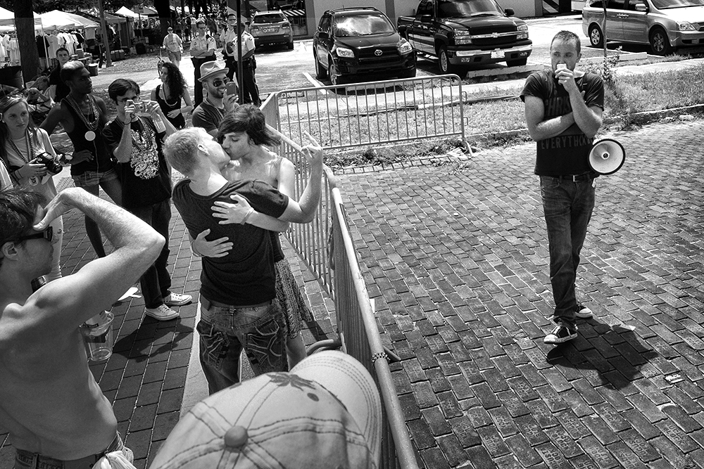 Opposing forces. The men in an embrace on the right show their contempt for the man on the right who is proselytizing at the St Pete Pride event