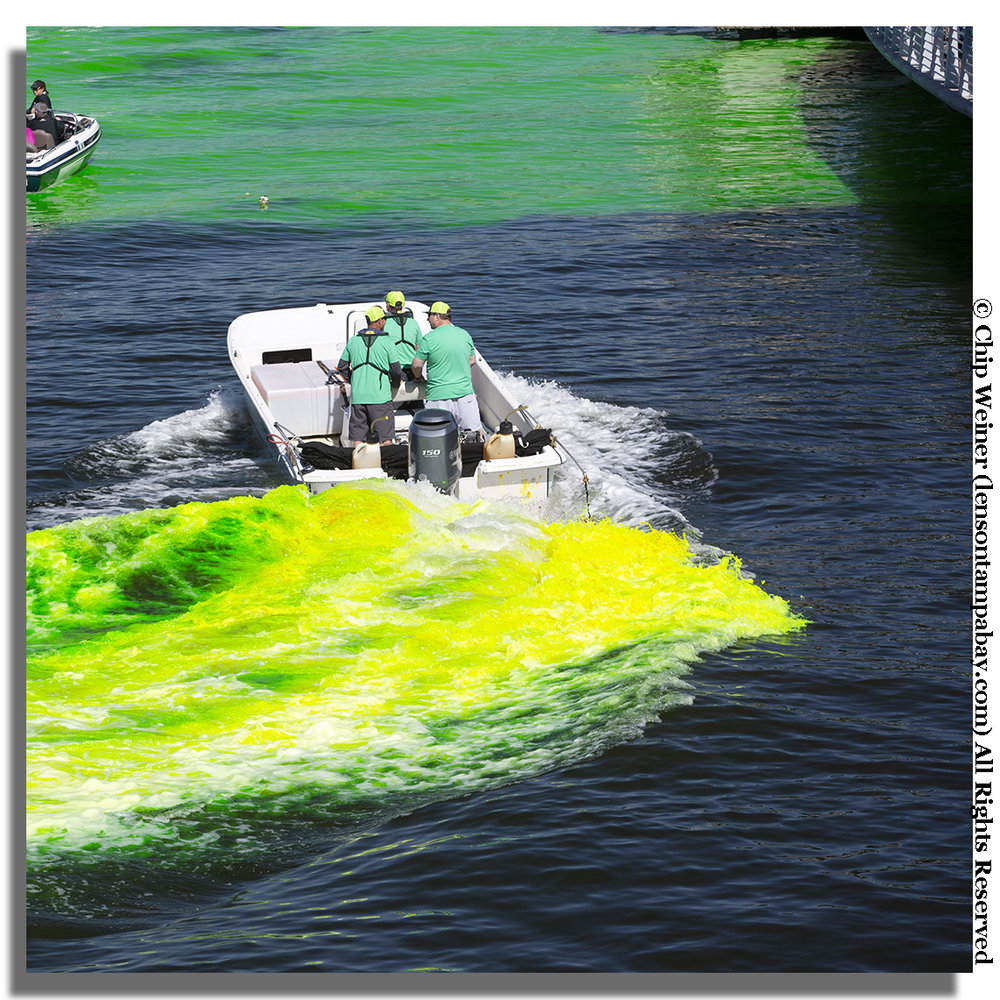 Two boats dropped the dye into the water and then turned it with their motors to turn it a bright Kelly green