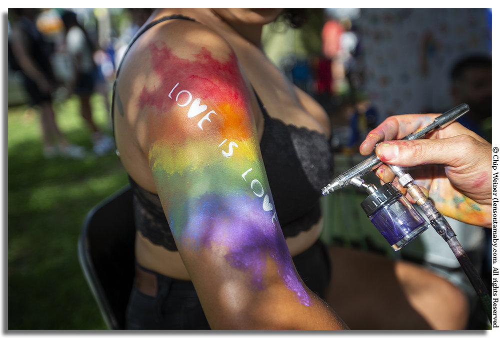 Devin gets a spray tattoo at the Morgan Malice tent with a sentiment heard often repeated at Saturday's gay pride event.