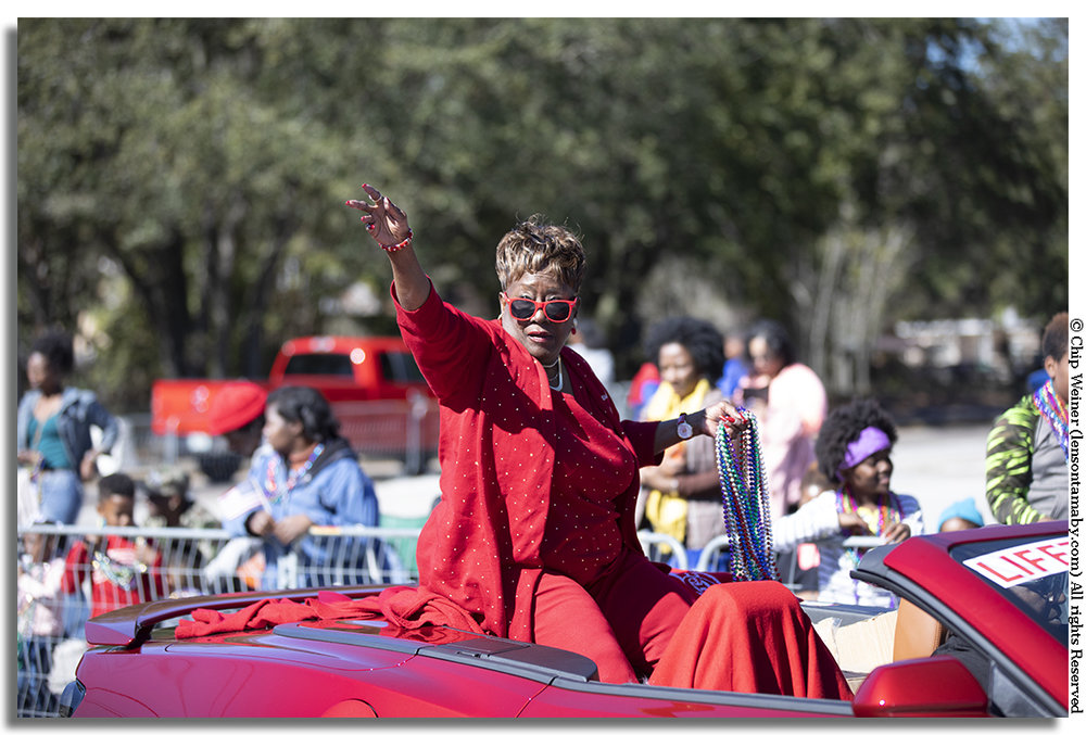 Parade Grand Marshall Dr Paulette Walker in her red sunglasses and red attire rides in a red convertible!
