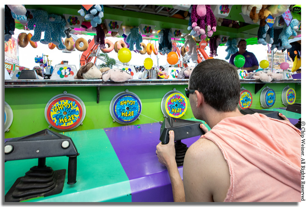 """"""" Want a prize? Pick your size! Winner every time """" says the raspy voice over the PA system at this game where players shoot water at a target which inflates a balloon. The first balloon to pop wins!"""
