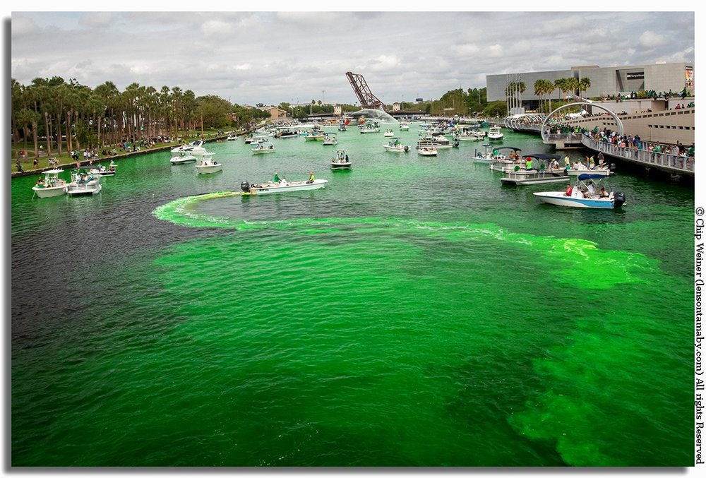 A boat zigzags back and forth dropping the yellow/green liquid dye into the water. The boats prop helps to churn and agitate the mixture.