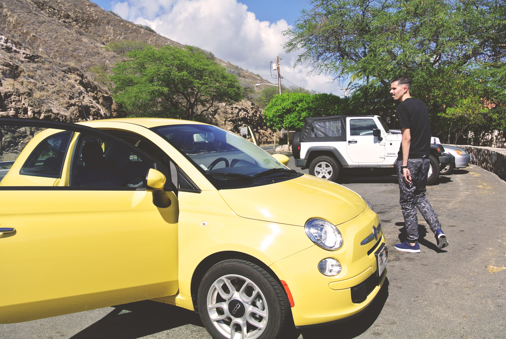 P with our rental, The Hawaiian Bee Fiat, on Diamond Head Road.