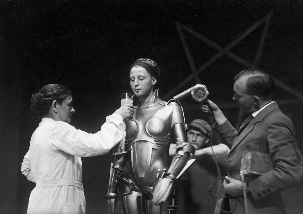 "The Maschinenmensch (German for ""machine-human"") from Metropolis, is a gynoid (female robot and female android) played by German actress Brigitte Helm in both its robot form and human incarnation. Named Maria in the film, and ""Futura"" in the Novel, she was the first robot ever depicted in cinema. Robot Maria's haunting blank face, slightly open lips, and pronounced female curves in the film have been the subject of disgust and fascination alike."