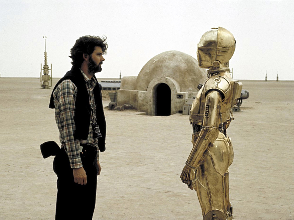 A young George Lucas confers with Anthony Daniels as C-3P0 on location in Tunisia, 1976.