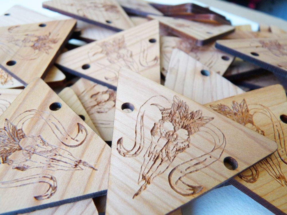 """Pampille triangle gravée en bois avec motif gravé pour agenda annuel du blog """"Le Monde est à Nous"""""""