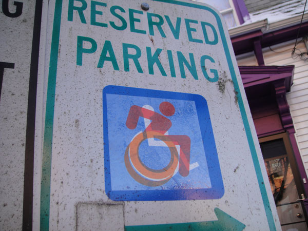 Accessible Icon 2.0 - A transparent orange symbol of a person in a chair to express personhood, leaning forward with a double wheel to suggest movement.