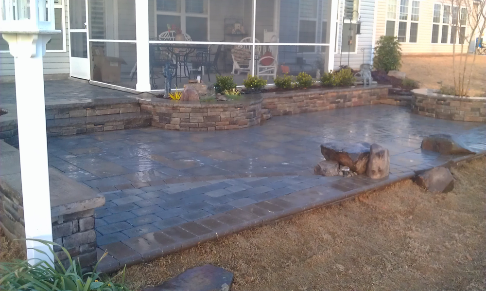 The boulders, stone and pavers have been set in place and polymeric sand brushed into the cracks between the pavers. The patio has been hosed down to help the sand bond and form a permanent seal.