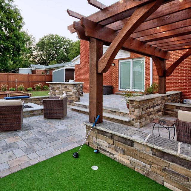 Here you can see more of the putting green and cedar pergola, and catch a glimpse of the raised garden beds in the background, behind the fire pit area. Also have to point out that crazy amazing texture on the cap stones of the seat wall! What?!?!😍 . . This outdoor living space was designed and installed by the @outdoorartisan team. Photo by @brucesaundersphotography. . . . #brucesaundersphotography #outdoorartisan #techobloc #patios #patio #backyardgoals #outdoorspaces #outdoorroom #pergola #pergolas #backyarddesign #backyardideas #backyards #firepit #firepits #stonewalls #seatwall #grillbar #outdoorlivingspace #outdoorspace #outdoordecor #backyardliving #outdoorentertaining #patiodesign #paverpatio #pavers #patiolife #raisedgardenbed #raisedgarden #outdoorentertaining #puttinggreen