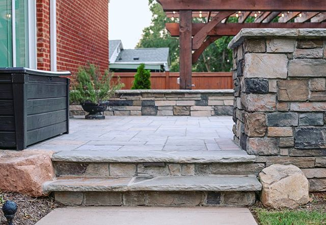 Step on up! A closeup of the side access that leads to the upper patio and grill area of this week's feature project. 😍 this particular combination of natural and manmade materials. We used Techoblu pavers, flagstone caps and step treads, Boral - Country Ledgestone veneer, and boulder accents. . . This outdoor living space designed and built by the @outdoorartisan team. Photo by @brucesaundersphotography. . . #brucesaundersphotography #outdoorartisan #techobloc #outdoorspaces #patiovibes #pergolas #hardscapes #patiogarden #backyards #stonesteps #seatwall #stonestairs #retainingwall #stonepatio #patios #patio #paverpatio #patiolife #outdoordesign #outdoorsteps #outdoorpatio #patiostyle #outdoorlivingspace #backyarddesign #outdoorentertaining #patiodesign #outdoorroom #flagstone #outdoordecor #boral