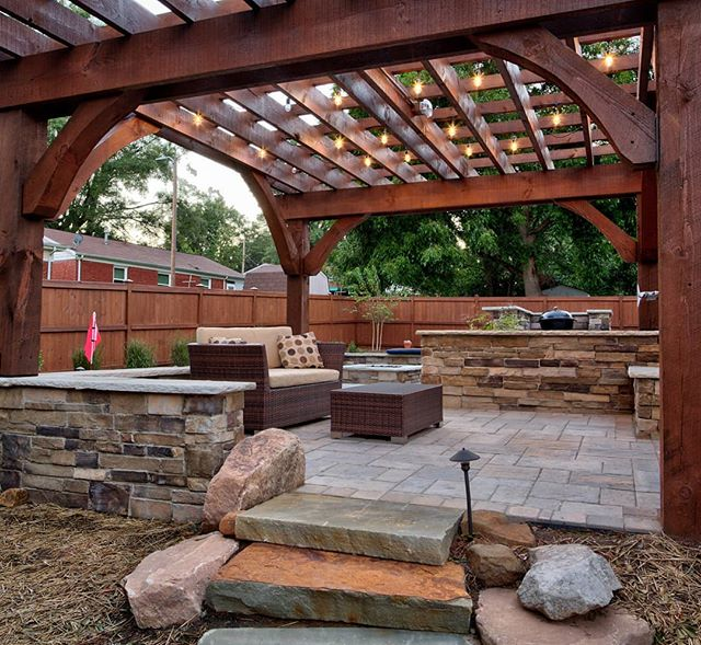 Here's the lower patio seating area with Techoblu pavers and Boral veneer walls, capped with flagstone. The custom cedar pergola really completes this area, and makes it feel like it's own room. Although the grass hasn't quite recovered, I wanted to also show the natural stone slaps that give access to lower side yard. . . In the background, you can see we built a C shaped bar around his current grill. This gives the #grillmaster some prep space, and allows for family and friends to sit at the bar while he's grilling, to advise and sample.😋 We also left space for a new grill, since he was planning to upgrade soon. Note: The bright orange flags belong to a putting green on the other side of the wall. You can see it best in my last post. . . This outdoor living space was designed by Josh and installed by the @outdoorartisan team. Photo by @brucesaundersphotography . . . . #brucesaundersphotography #outdoorartisan #techobloc #outdoorspaces #patio #patioseason #outdoorspace #patiodecor #patiodesign #backyardgoals #outdoordecor #outdoorroom #pergola #pergolas #backyards #hardscapes #hardscape #hardscaping #outdoorlivingspace #backyardliving #outdoorlighting #landscapelighting #paverpatio #charlottecontractor #customcarpentry #moderncraftsman #outdoorentertaining #landscapeconstruction #boral