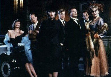 left to right: Miss Scarlet (Lesley Ann Warren), Colonel Mustard (Martin Mull), Mrs. White (Madeline Kahn), Mr. Green (Michael McKean), Wadsworth (Tim Curry), Professor Plum (Christopher Lloyd), and Mrs. Peacock (Eileen Brennan)