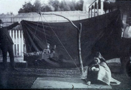 Franz Boas and George Hunt holding up a screen for a staged photo in the field.