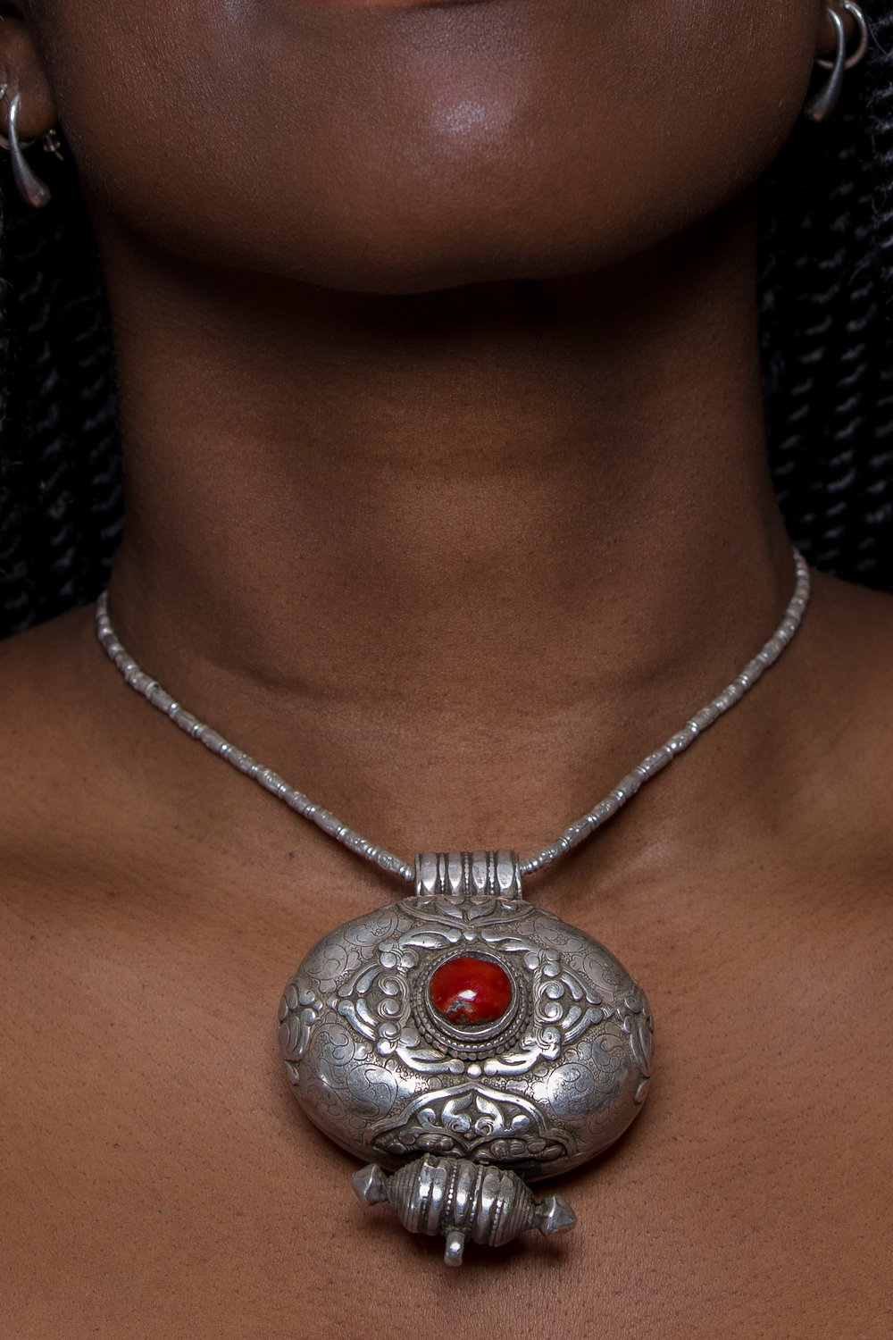Silver Tibetan Ga'u box with coral. Worn in all areas of Tibet, oval shaped boxes were particularly favored by women in the southern border areas of Tibet, in Sikkim, and Bhutan. Jewelry: Arjuna/Toni Zito    Model: Aita     Light: Profoto