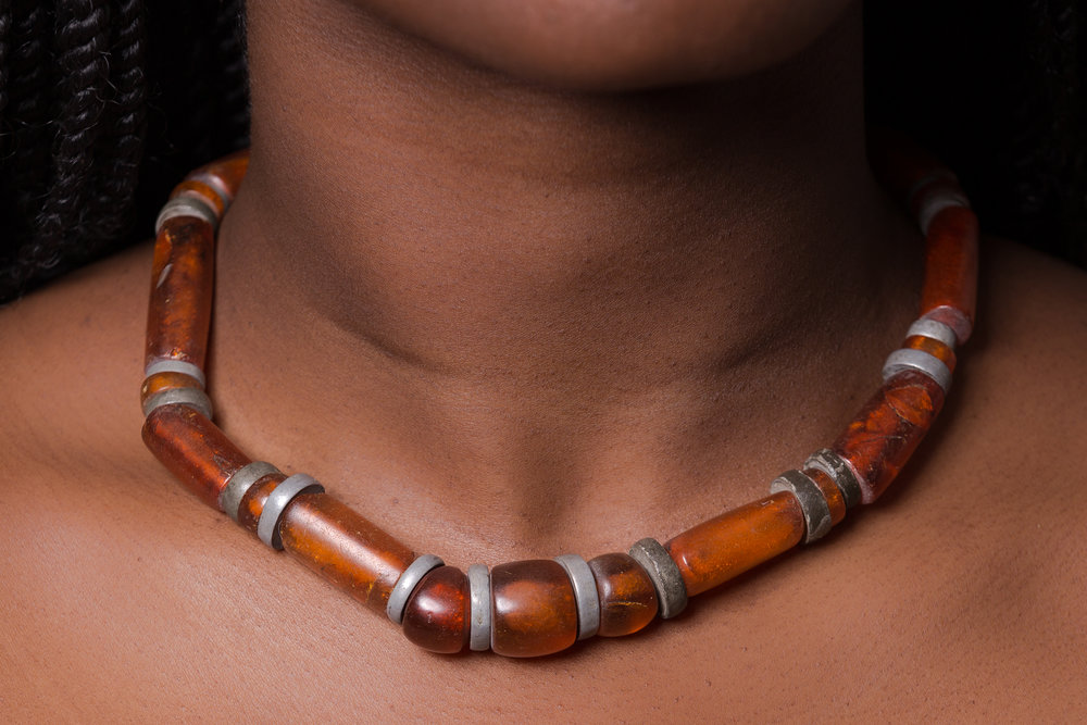 "Burmese amber is relatively rare and has been mainly exported to China where it has been used since the Han dynasty (206 B.C. to 220 A.D.). Worn by women of the Mizo tribe who live in the hills near the Burmese border. The necklace, known as ""thihna"" or ""puan chei mala"" typically consists of alternating long and short amber beads, sometimes interspersed with relatively thick aluminum disc spacers. Mizos appreciate Burmese amber's reddish to dark brown color and mottled appearance. Jewelry: Arjuna/Toni Zito    Model: Aita     Light: Profoto"