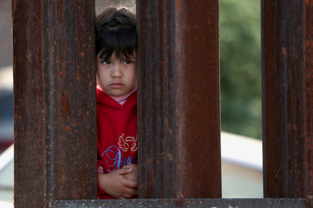 A child in Mexico at the U.S.-Mexico border fence looks into Nogales, Arizona.