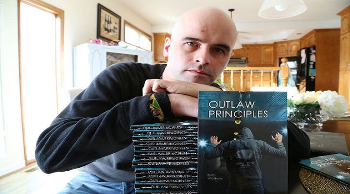 "Author Ryan Wickham with his book ""Outlaw Principles"""