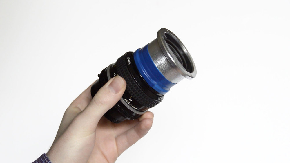 The adapted Lomo Fisheye No. 2 lens mounted on an old school Nikkor 28mm. + Hand.