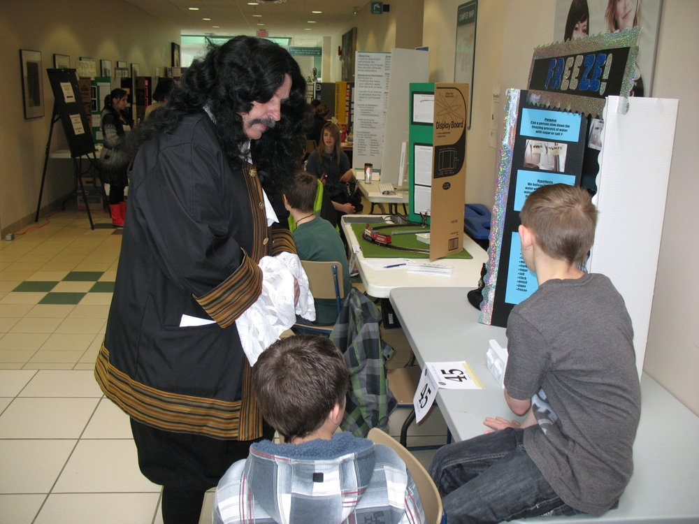 "Praxis Science Fair: Famous 17 Century Scientist ""Robert Boyle"" visits with the participants."