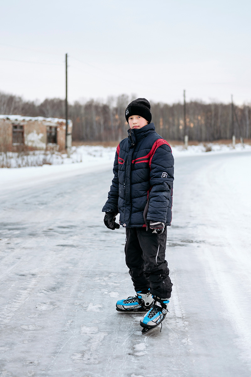 A boy ice skating on the frozen countryside road between Omsk and Uval'naya Bitiya, Russia.