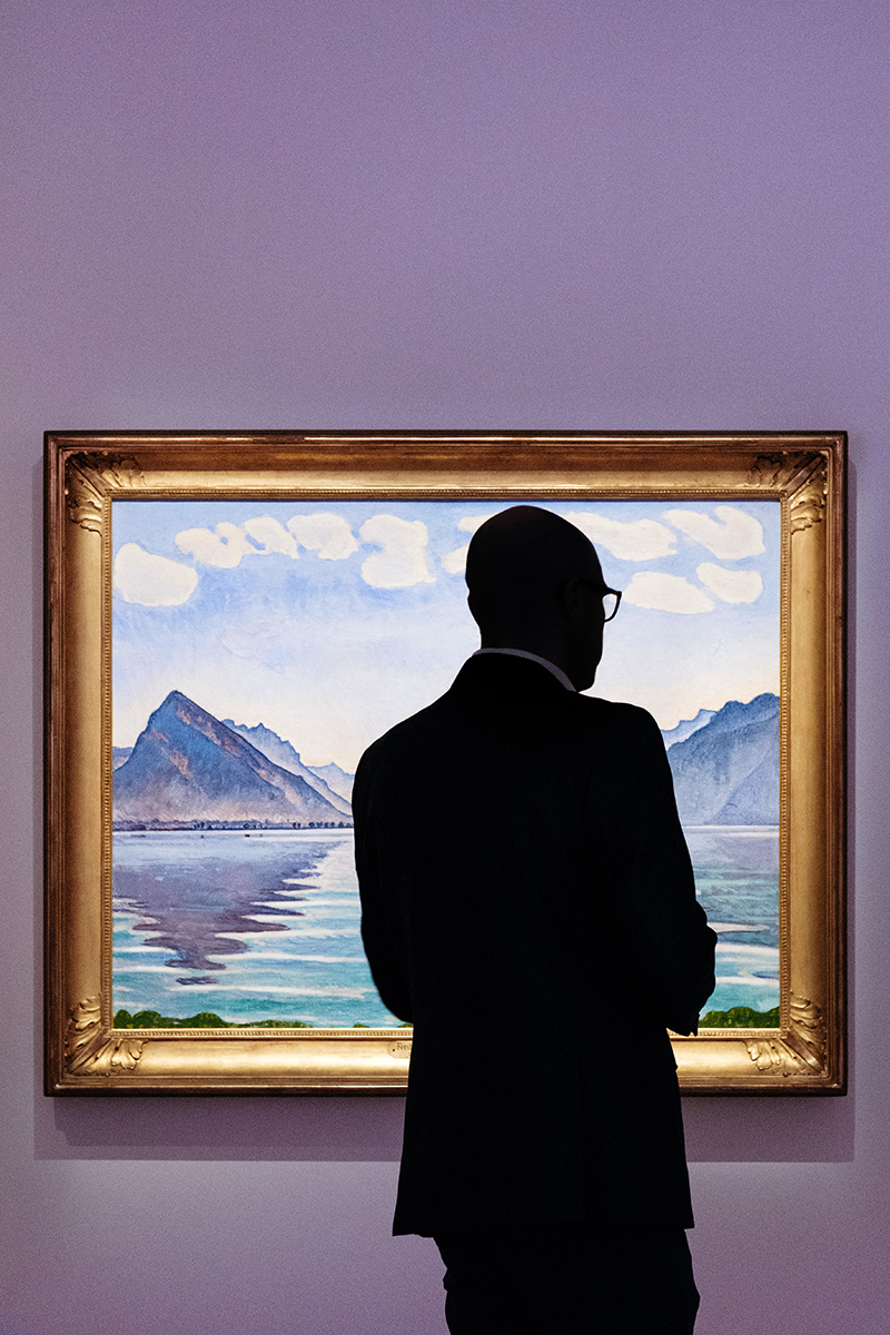 "A visitor observing Ferdinand Hodler painting ""Lake Thun, symmetric reflection"" on display at the Rath museum in Geneva during the Hodler Parallelism temporary exhibition."