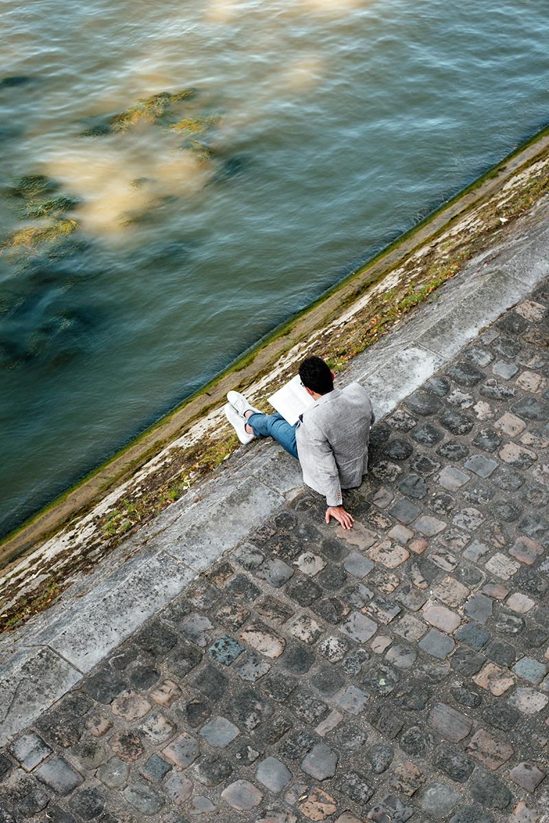 A Parisian reading a book at Quai de Montebello on the Seine river banks.