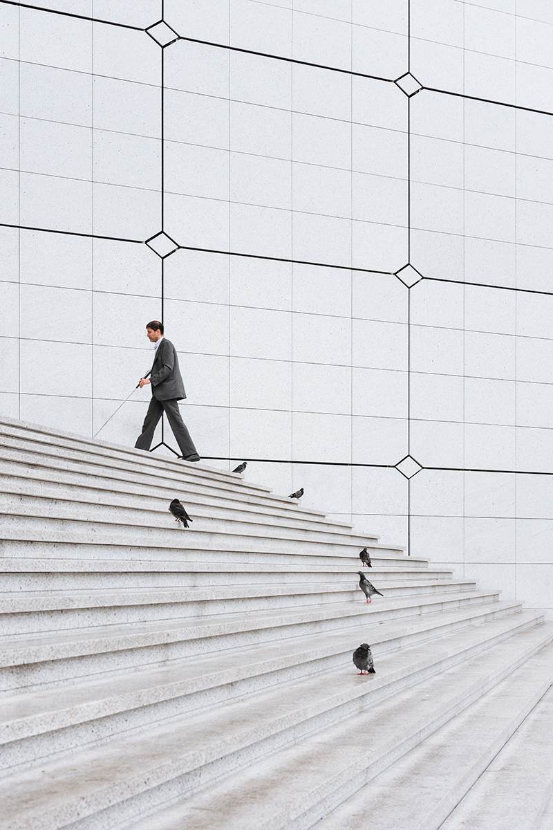 A visually impaired man going up the stairs of La Grande Arche de la Défense in Paris.