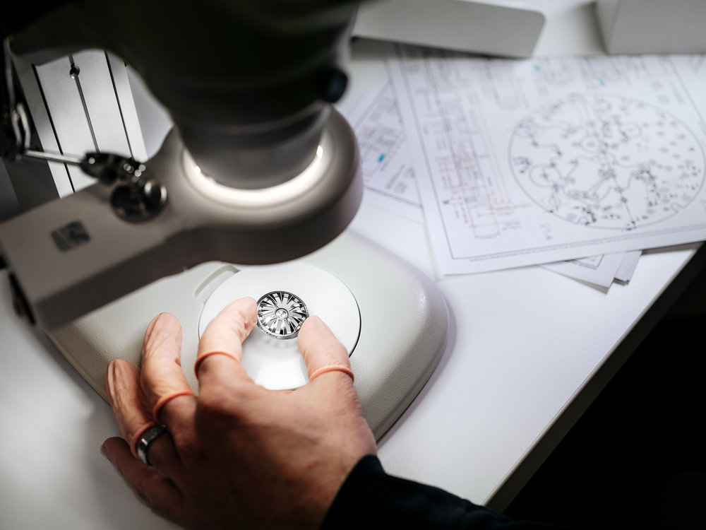 Inspecting a component, the platinum sector of the winding rotor of the Horological Machine No.7 - Aquapod at the MB&F atelier.
