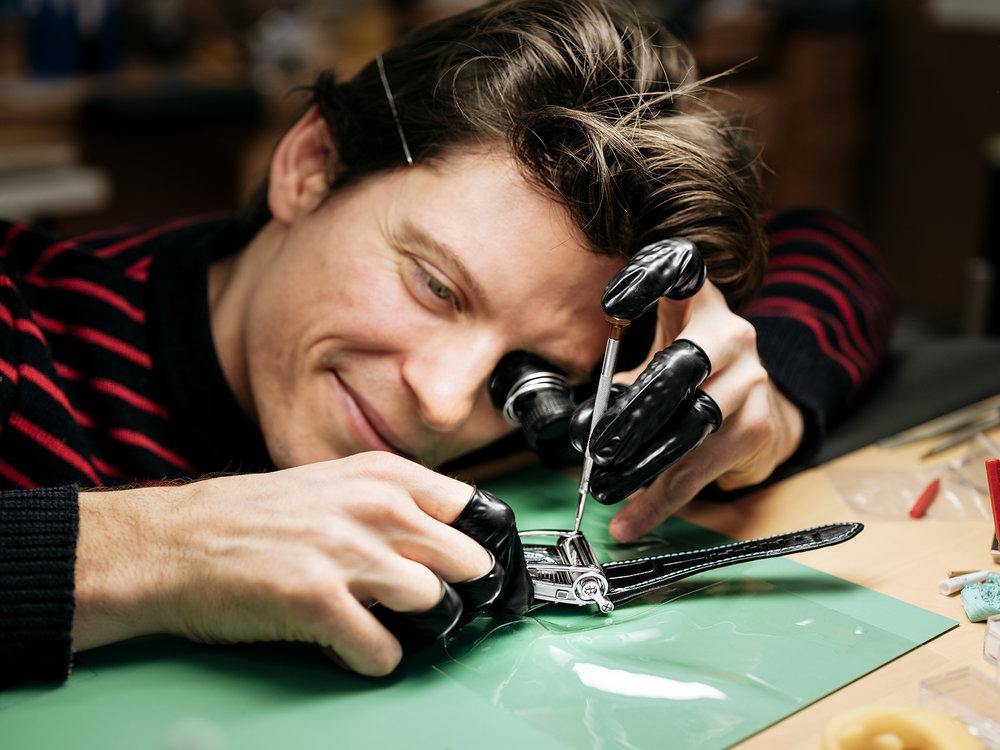A craftsman attaches a component to a MoonMachine 2, a watch by MB&F and noted Finnish horologist Stepan Sarpaneva with a moonphase display.