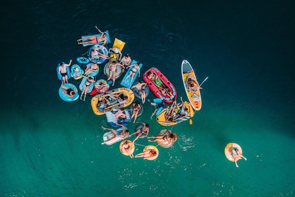 Summer at Pointe de la Jonction, twenty-nine people on various floating devices on the Rhône river.