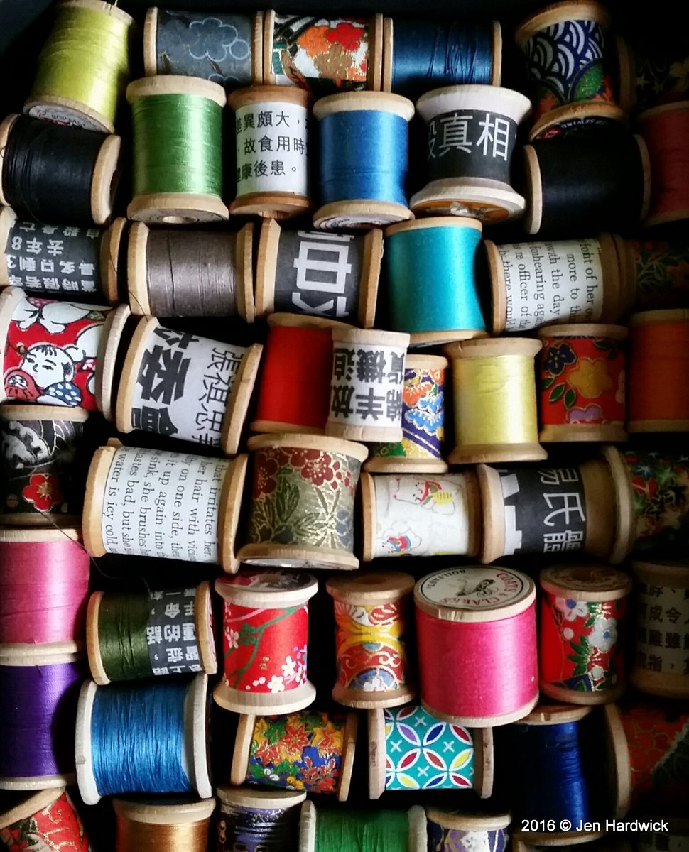 Wooden spools with thread or paper.