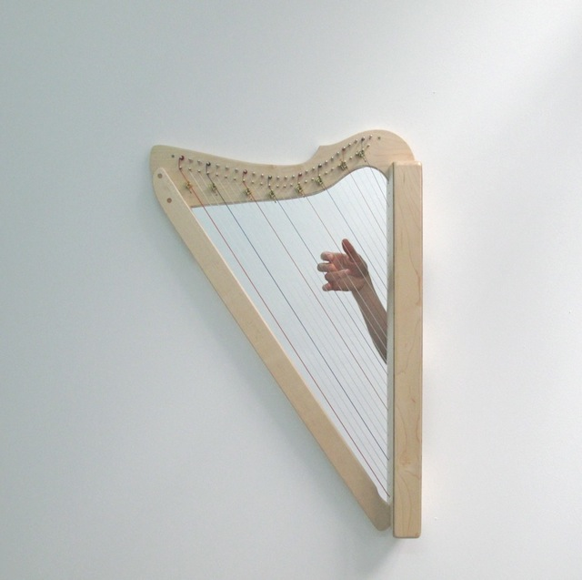 When you approach the intruding precarious wall of Comunitas (Wall/Harp) you become aware of its temporariness, built and designed with functionally as its DNA . This prosthetic structure contains within its liminal space, a small harp is snugly secured in a cut out, acting as a transitory border between either sides of the wall. The architecture of the arrangement prohibits willing players to cradle the harp into their body, denying them the ability to place both hands on either side of the strings. Here Guillerme E. Rodriguez Rivera stages a rather cruel trick on the visitor. The dumbness of this pre-empted relationship, existing between the anticipation of the visitor and the potential of the situation, only appears after the sensuality of the presence of the instrument has taken its effect on its subject—like a siren calling sailors to a rocky cove.  This is a radical form of hospitality staged by Rodrigeuz, who invites you to consider an unusual way of belonging together. The work suggests that two people play a duet from either side of the wall. Without the ability to see each other, the only sensory call and response between the players comes from the sound of the instrument. Will frustration and defeat ensue if we are to choose this optimistic but naive position when approaching the equation of community and collaboration? Despite this, inherent in the work is the cynic's core position; optimism for the small probability of good to emerge in the world. Rodriguez proposes this provocative scenario by ultimately seeing some prospect for certain players to find harmony within this obtuse triangulation.  Ludic, a term used by Rodriguez to describe his work, comes from the writer and philosopher Nassim Nicholas Taleb, which is used to define games and play as scenarios in order to consider chance as one of the central guiding forces of our universe. Chance is central to most of our own lives and their winding turns. The unforeseen affects us by asking us to alter course and to adapt in relation to it. Or, in a negative sense of the position, to censor what we do, so that we behave in a way to know our outcomes, marking us as fearful of the irregular. Rodriguez harnesses these intuitive impulses as a guiding force, hacking the already made and redefining their intended uses to produce varying results of success and failure from a user generated perspective.  Reminiscent of modern art's leaders, such as Giaciometti's board game On Ne Joue Plus (1932), Duchamp's chess match versus Cage (1968) or Hacke's MOMA Poll (1970), the potentiality of chance is exploited as the work's central force, taking both a submissive but also freeing position towards risk. Also introducing the act of joy, liveliness and performance into the gallery space, Rodriguez references a geographically closer canon of artists such as Oiticia's Eden (1969), Clark's Sensory Masks (1971) or Pape's Ttéia Cuadrada (1976), who also invited the participation of the visitor in the work, allowing for a reactivation of the gallery's neutral space.  Jesse McKee