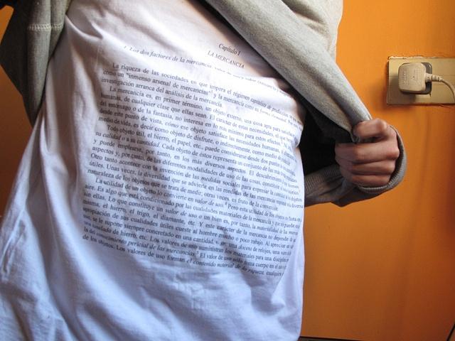 """Camiseta Autoexplicativa (entrevista con Laura Artigas)  Esse é o primeiro de três posts dedicados a artistas que conheci em Buenos Aires. Inauguro com uma entrevista ping-pong com o porto-riquenho Guillermo Rodriquez, 26 anos. Ele estudou arte em San Juan, Londres, e agora em Buenos Aires. Uma de suas obras usa a boa e velha camiseta branca como suporte. Ele estampa cada uma das páginas do famoso texto """"O Capital"""" do Karl Marx em camisetas e as vende. O plano é o seguinte: """"a mercadoria, explicar a mercadoria"""". No papo a seguir ele me conta de onde tirou essa ideia. Para a gente entender o seu universo: quem são os artistas que você admira e que te inspiram? As influencias são muitas e variadas. Vão desde do reggaeton """"La Gasolina"""" do (conterráneo) Daddy Yankee até a ética de Spinoza (!), sei lá. É uma lista em eterna mudança. Por que você escolheu a camiseta como suporte para esta obra? A camiseta tem uma relação direta com o corpo do espectador. O espectador deixa de ser espectador tão logo ele veste a camiseta. O design (neste caso a moda, a roupa) é sempre uma boa ferramenta para expandir a arte a outras esferas; como a arquitetura está para a performance, por exemplo. É divertido propor um diálogo entre diferentes disciplinas. Por que escolheu """"O Capital""""? Foi uma revelação (risos). A mercadoria (a camiseta) ilustrando o texto que descreve a forma como ela mesma opera. O resultado é um efeito loop. E como o ritmo de suas vendas determina seu ritmo de produção acentua esse aspecto cíclico. Cada peça é única, né? É. Cada página é uma camiseta ou cada camiseta é uma página. A versão em inglês tem mais de mil páginas. Mesmo que pareça muito exclusivo e que haja só um exemplar de cada uma, a quantidade de páginas problematiza o conceito de 'edição limitada"""". Onde as camisetas são vendidas? Geralmente em exposições de arte. Tenho vontade de vendê-las em lojinhas de museus e outros espaços comerciais. Recentemente foram vendidas na The NY Art Book Fair no MOMA PS1. V"""