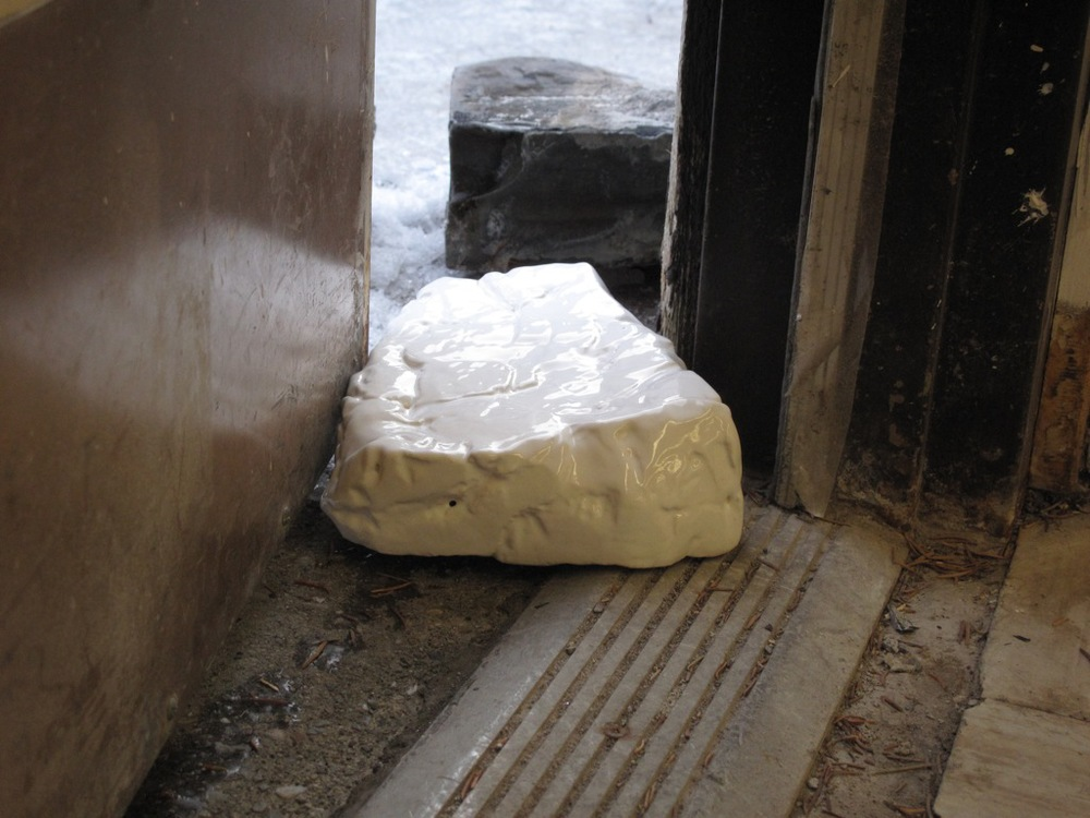A ceramic replica of a common rock is used as a door chock for the Banff Centre studio door during cigarette breaks. It is a common practice amongst the Banff Centre's residents and staff to keep heavy rocks near automatically locking doors in order to keep them open