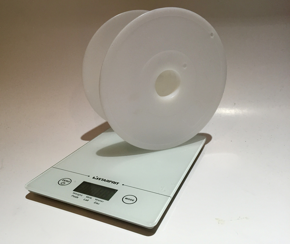 A digital scale weighs an empty 3D print spool