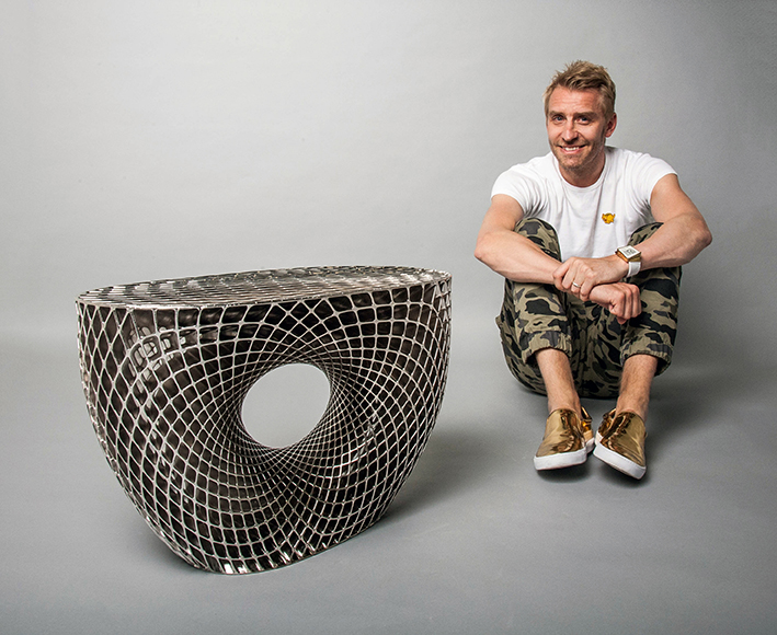 Janne Kyttanen sitting beside the beautiful 3D printed Avoid side table - with rhodium finish