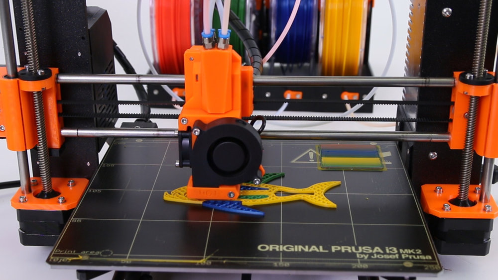 "Prusa's Quad extrusion concept in action. Note the ""wash"" area at the right rear where throwaway extrusions clean out the hot end"